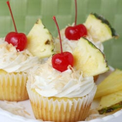 pina colada cupcake with cream cheese frosting and cherry on top