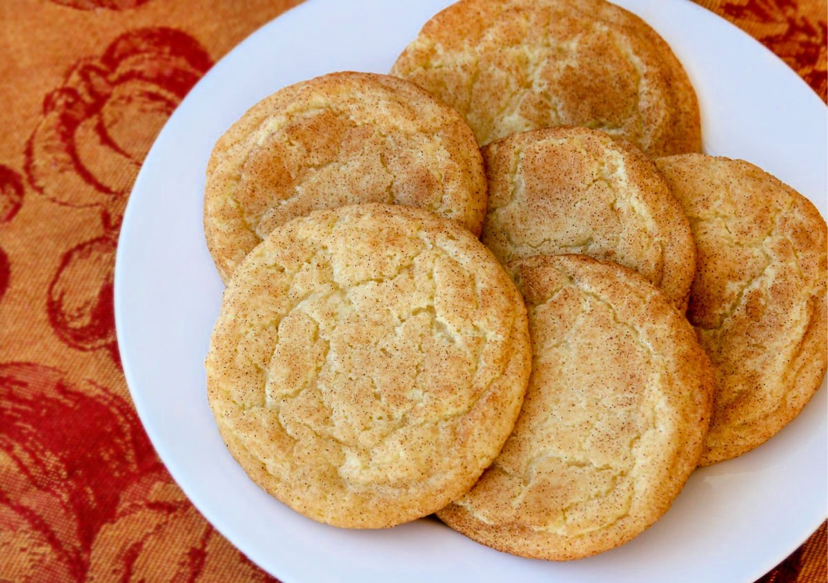 six cookies on a white plate with red and orange fabric underneath