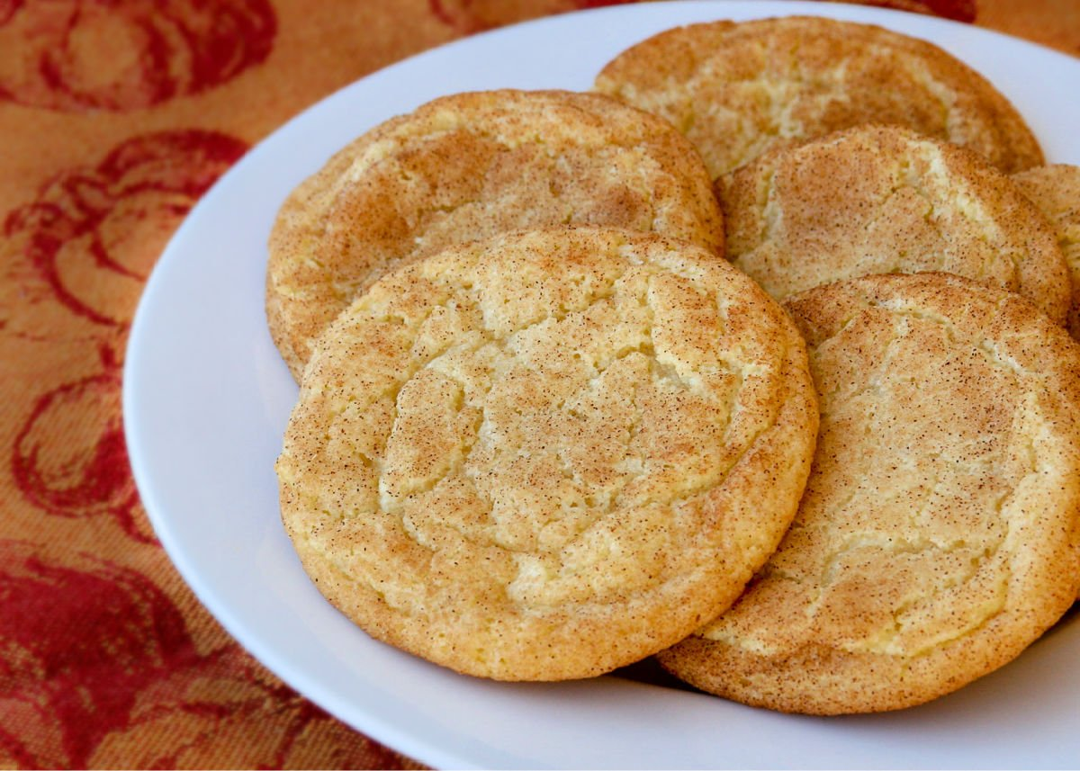 snickerdoodle cookies on white plate with orange and red napkin underneath