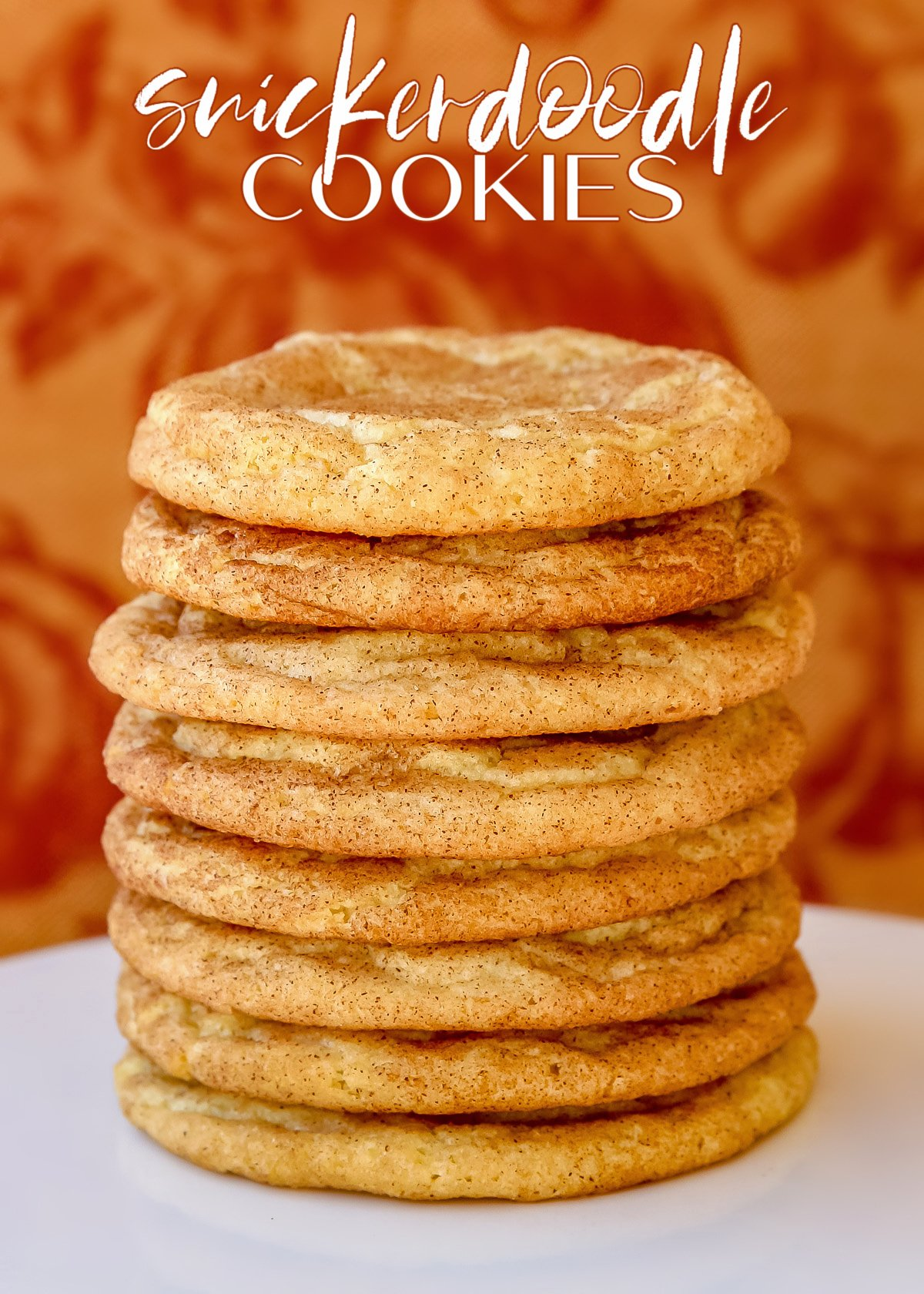 snickerdoodle cookies stacked high on white cake stand with fabric background and text overlay