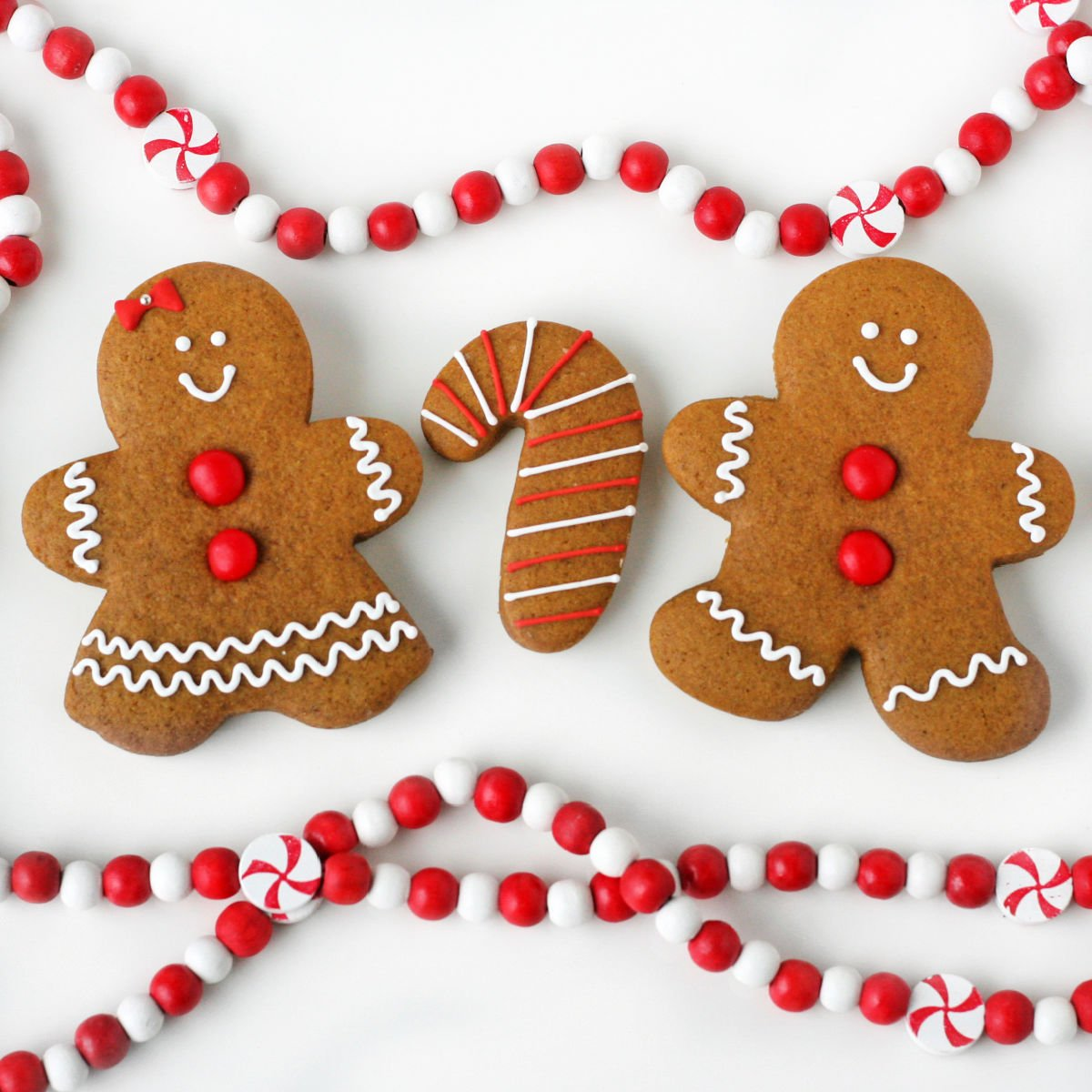 gingerbread cookies decorated with red hots and white frosting sitting on white surface with red and white bead garland