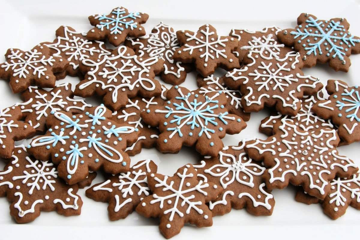 gingerbread snowflake cookies decorated with white and blue royal icing