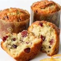 cranberry orange muffin split in half with orange peel text two whole muffins in background