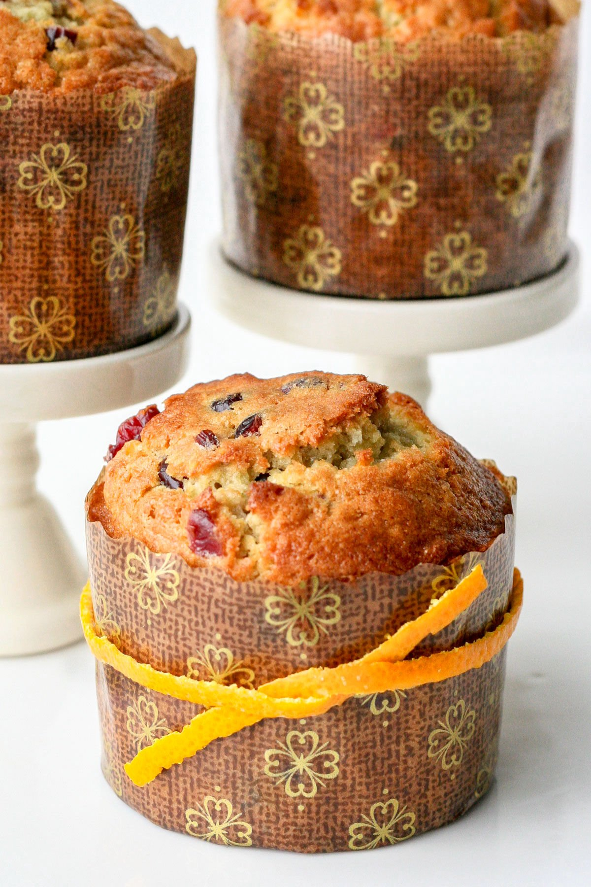 single cranberry orange muffin in paper liner with orange peel tied around it