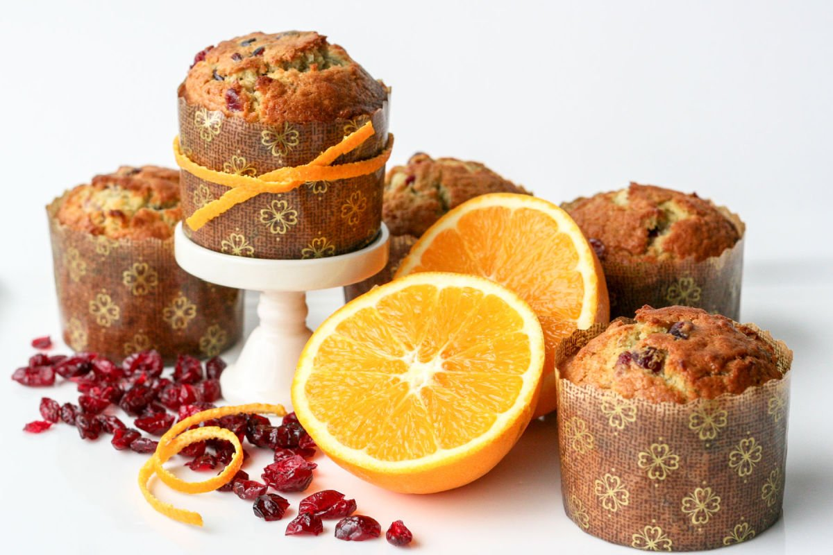 cranberry orange muffins with orange half and peels and dried cranberries scattered about