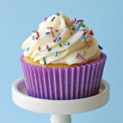 single vanilla cupcake on white cupcake stand with purple liner and pastel sprinkles