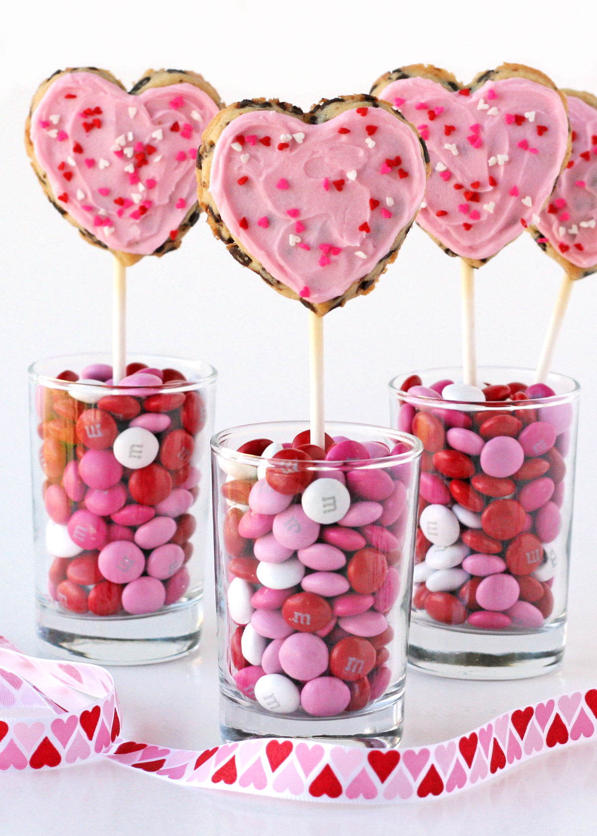 heart shaped chocolate chip cookies on sticks in cups with candy