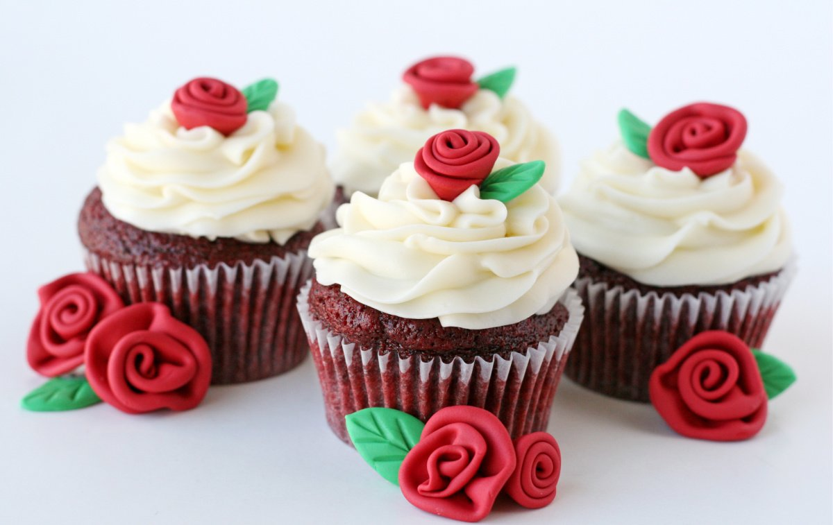 four red velvet cupcakes on a white backgorund