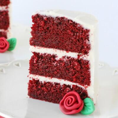 slice of red velvet cake with fondant rose on white plate square