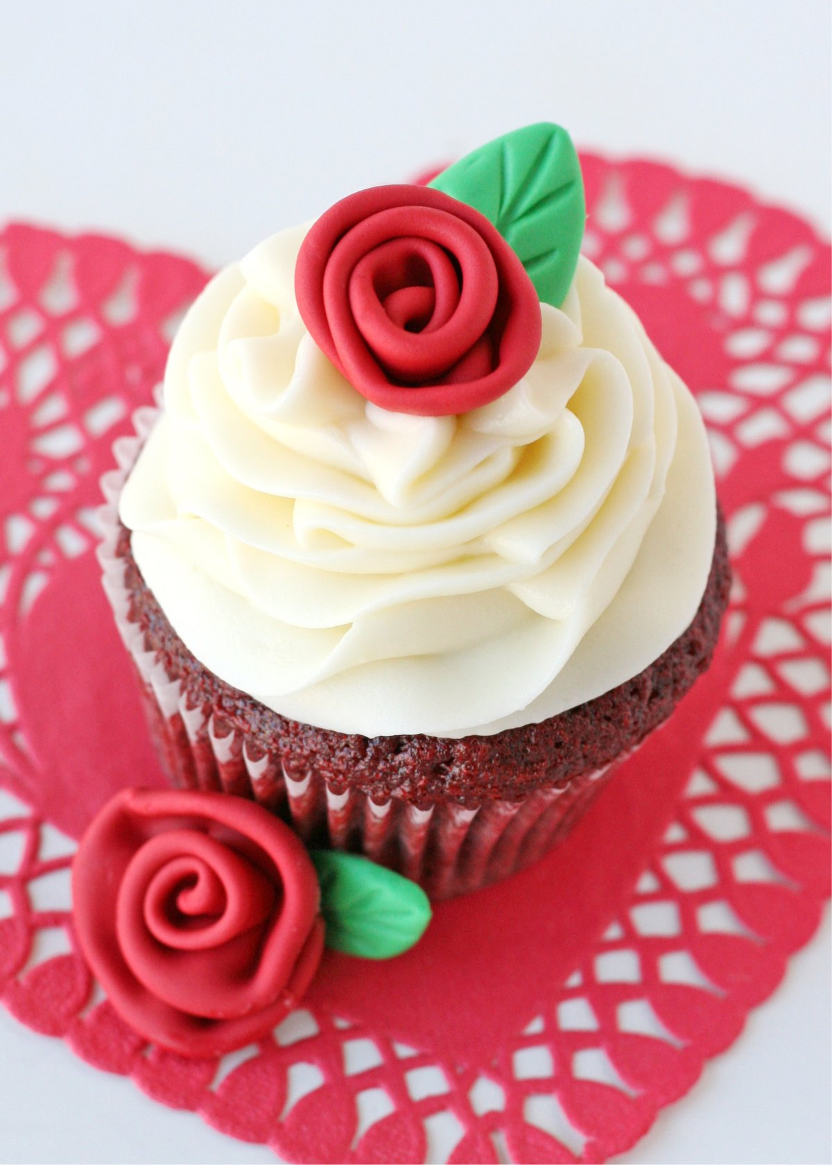 red velvet cupcakes on white background with red fondant roses