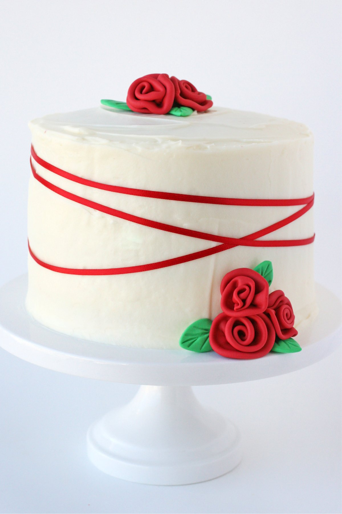 whole red velvet cake recipe on white cake stand decorated with red ribbon