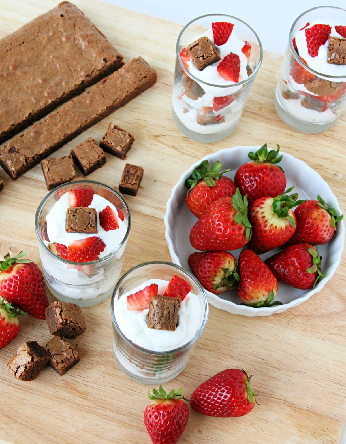 brownie strawberry shortcakes assembled in glasses with ingredients around them on a wood board.