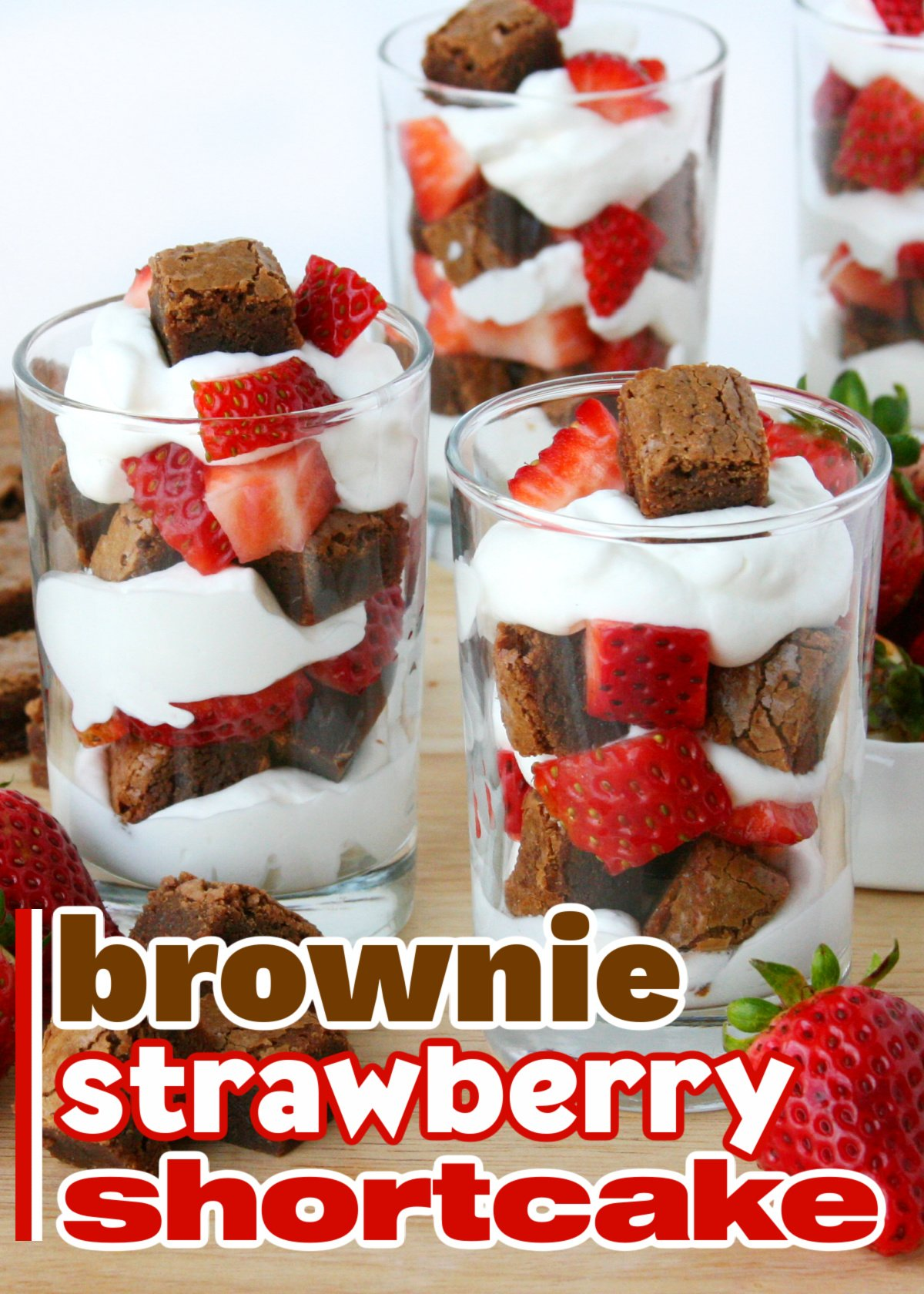 three small glasses with brownies chunks, whipped cream and strawberries layered in them. Title overlay at bottom of image.