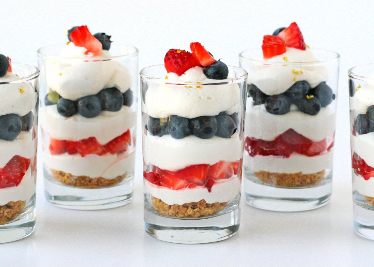 5 glasses with berries and cream and cheesecake.