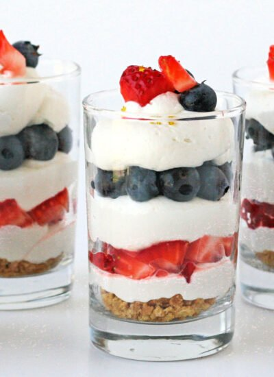 no bake trifle in three glasses layered with berries and cream.