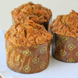 three pumpkin muffins recipe with cinnamon streusel on white cake stand