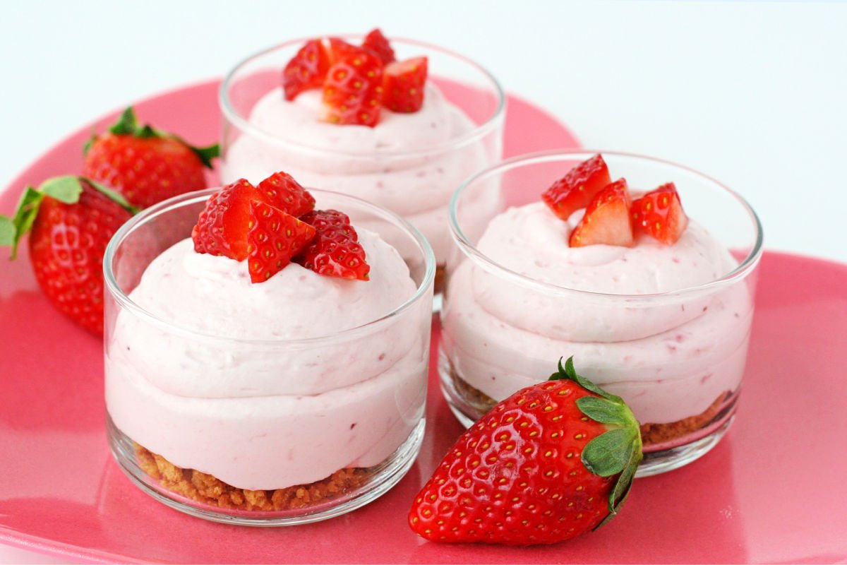 3 strawberry cheesecake mousse with graham cracker layer in small glass jars topped with fresh diced strawberries