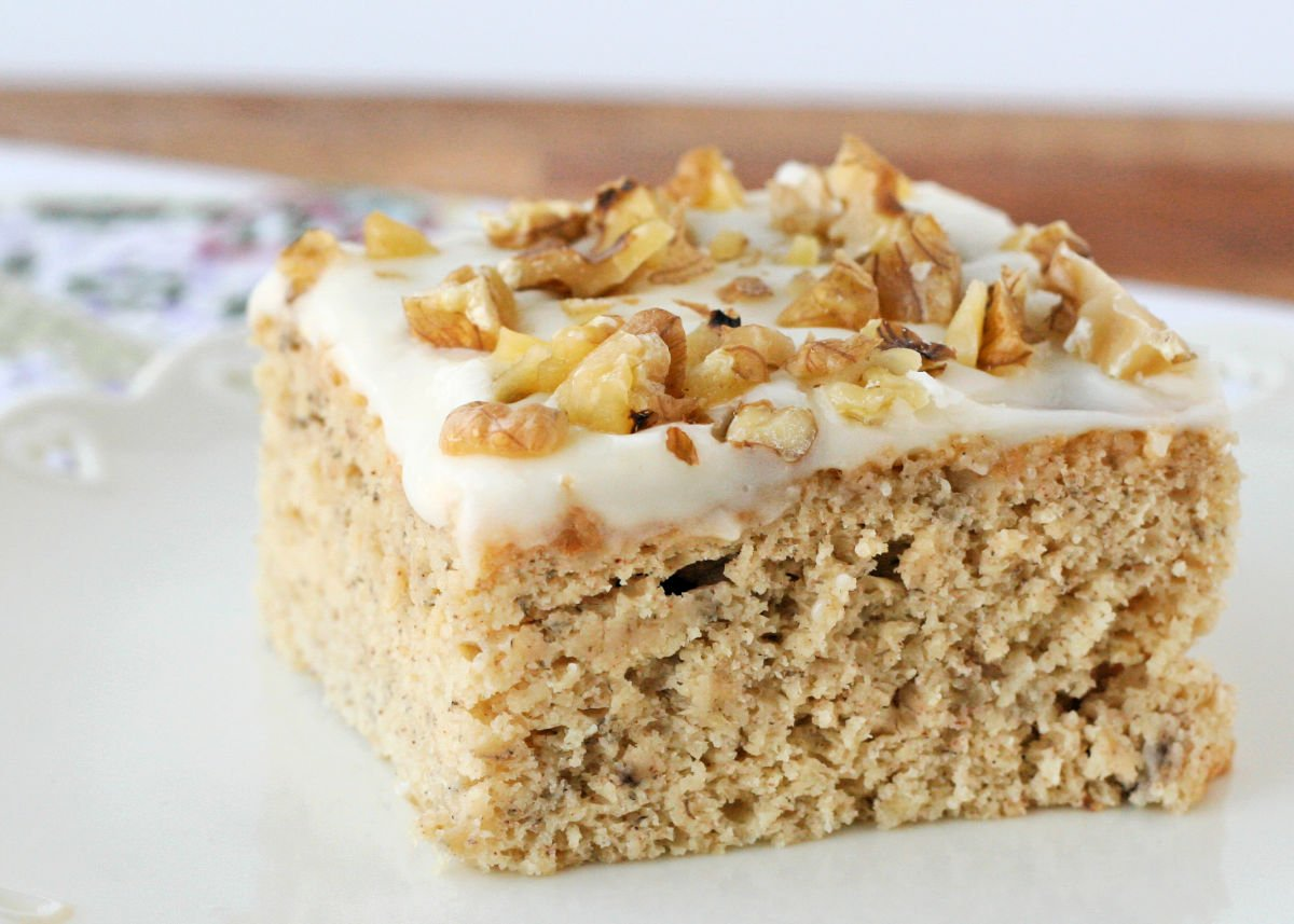 front view of a piece of banana cake on white plate topped with frosting and nuts.
