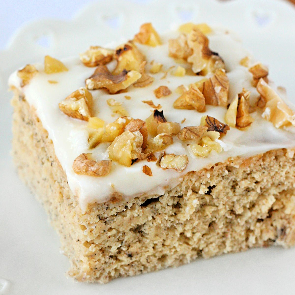 piece of banana cake with cream cheese frosting and walnuts on top sitting on white plate.