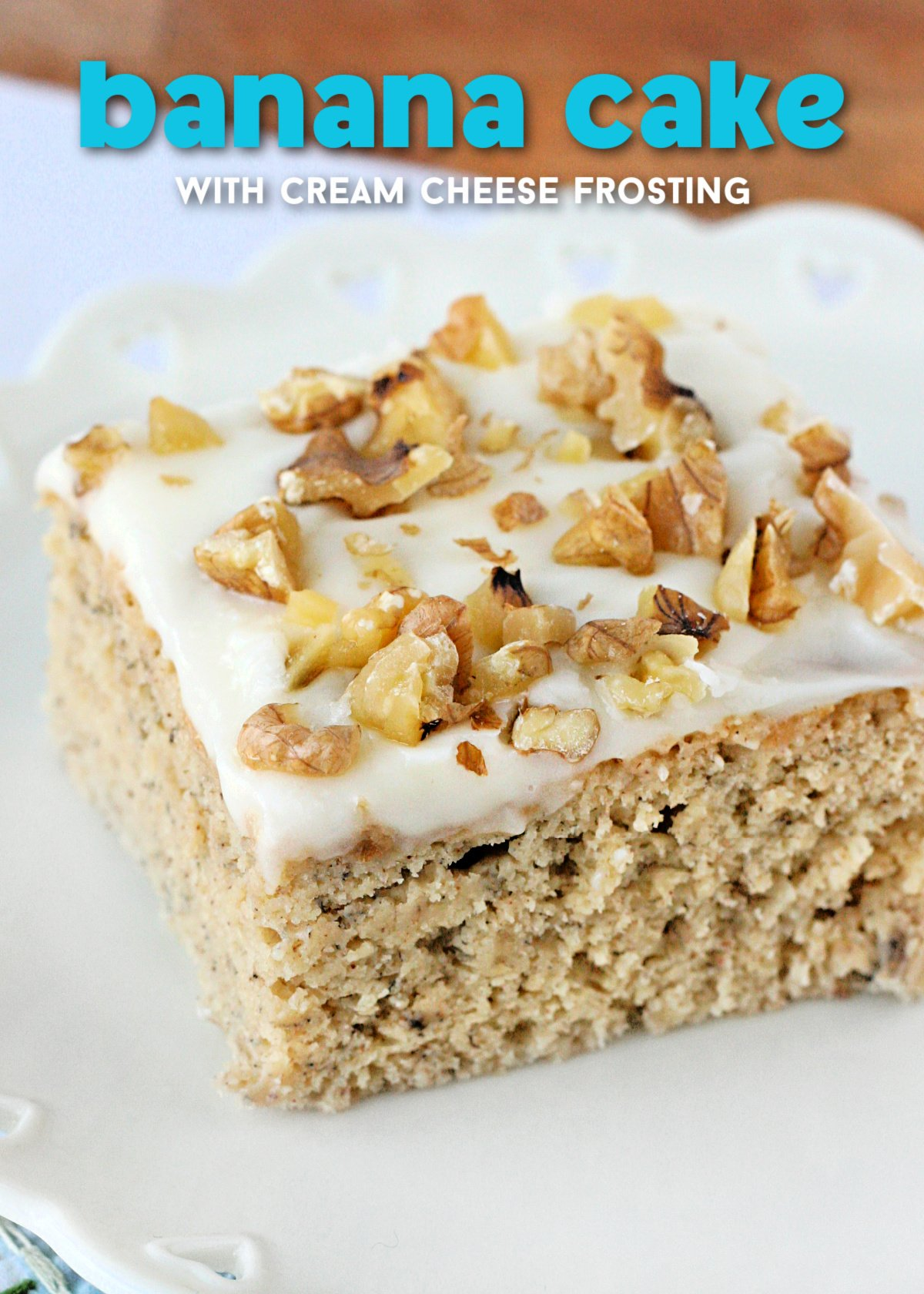 piece of banana cake with cream cheese frosting and walnuts on top sitting on white plate with text overlay at top of image.