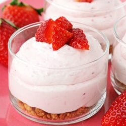 strawberry cheesecake mousse with graham cracker layer in small glass jar topped with fresh diced strawberries square