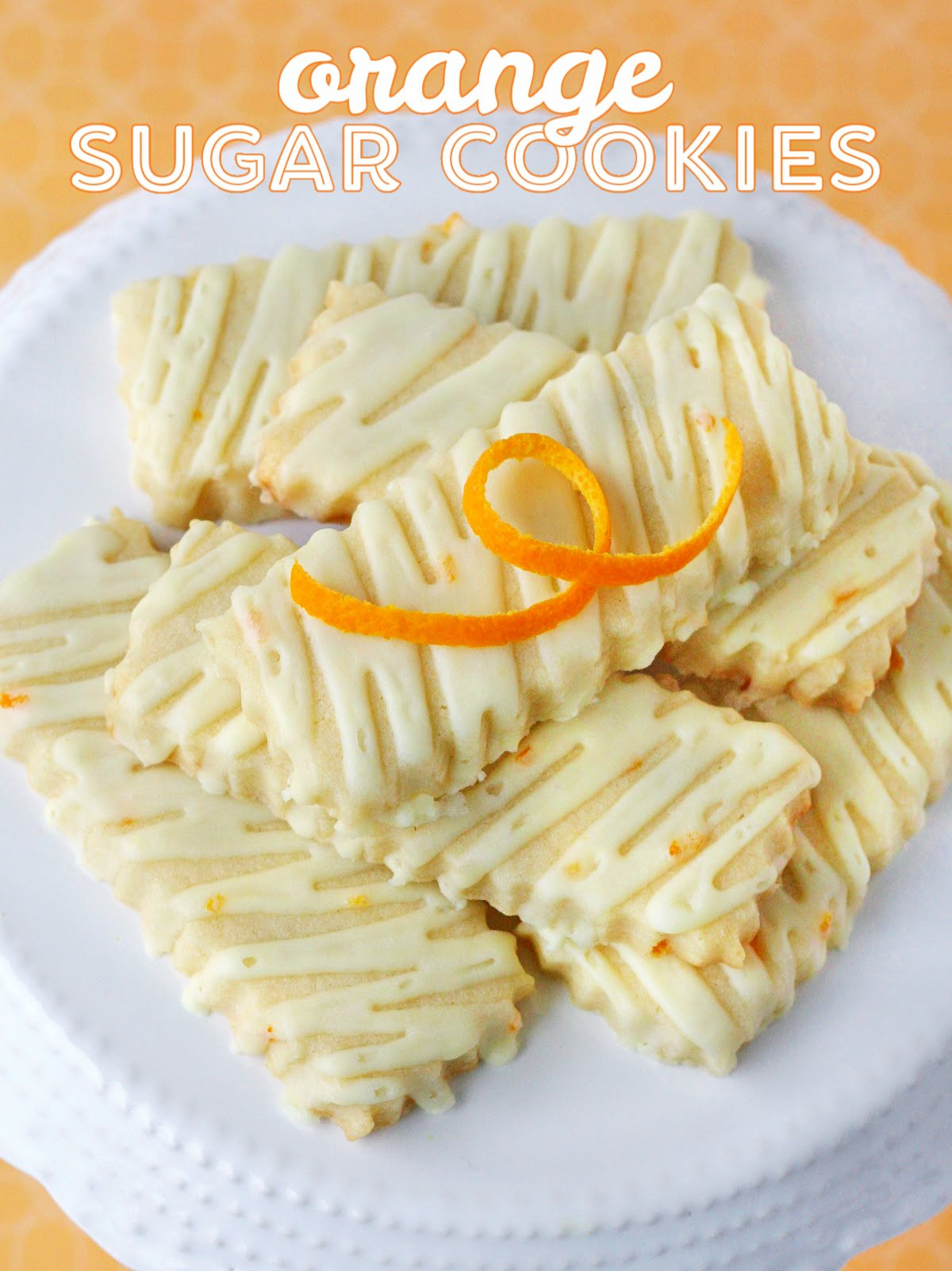 orange sugar cookies on white cake stand with title overlay at top of image.