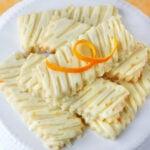 orange sugar cookies on white cake stand.