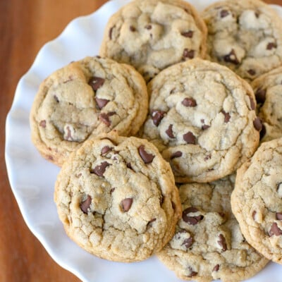 chocolate chip cookies piled on white cake stand with wood surface underneath square image