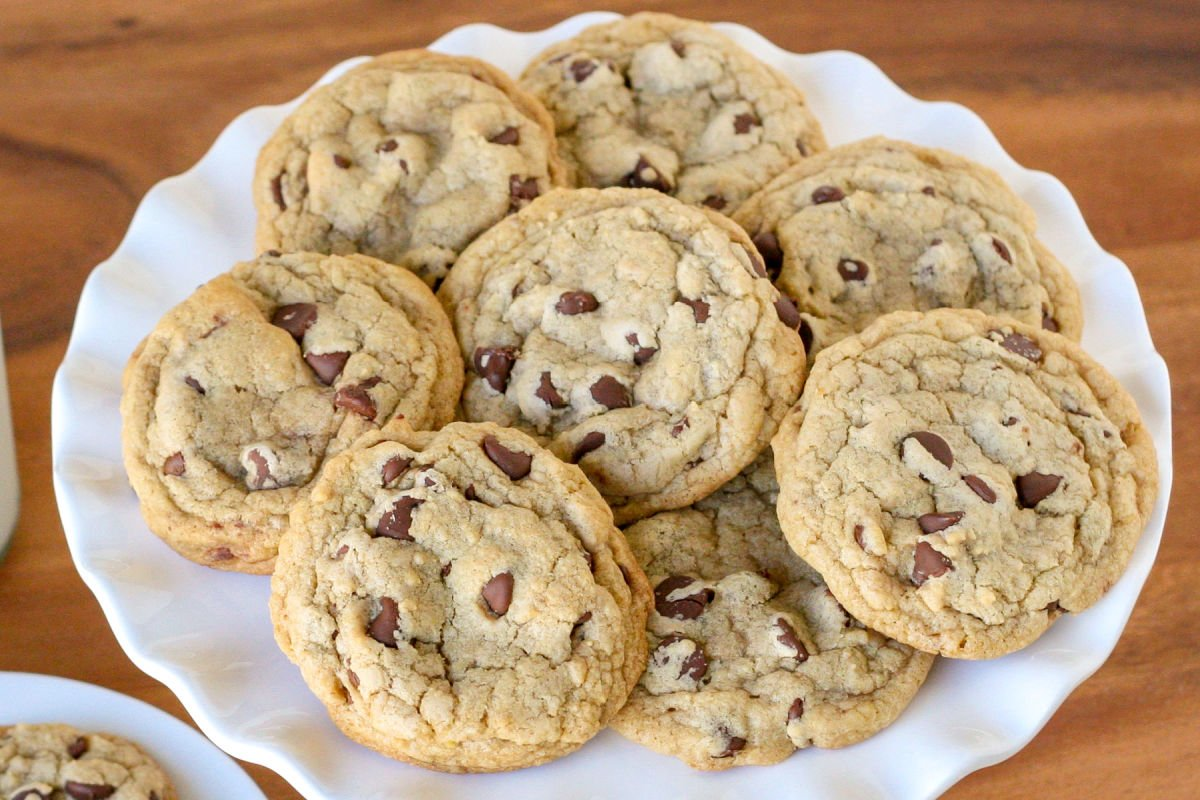 chewy chocolate chip cookies piled on white cake stand on wood surface