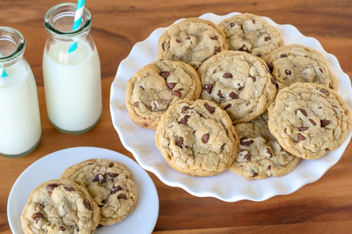 chocolate chip cookies on cake stand and on white plate on table top surface