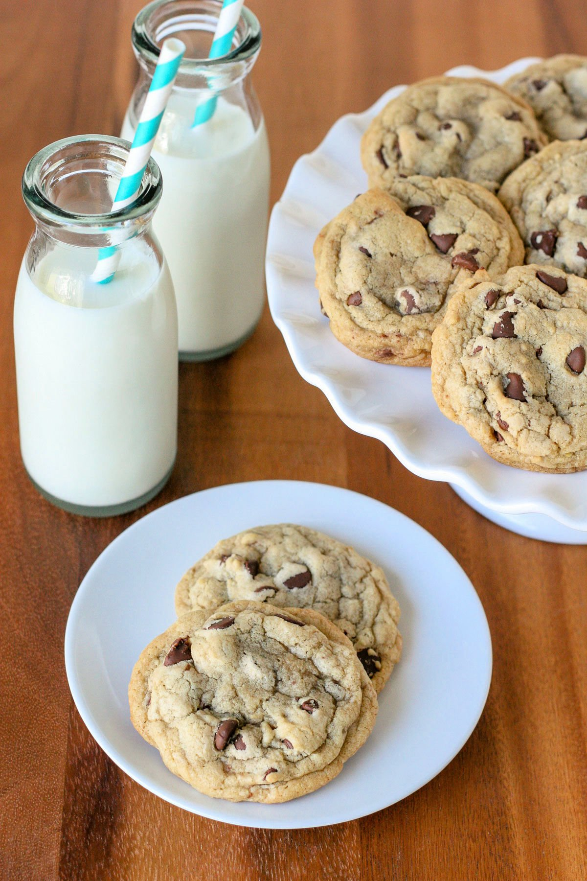 chocolate chip cookies on plate and cake stand with milk bottles in back