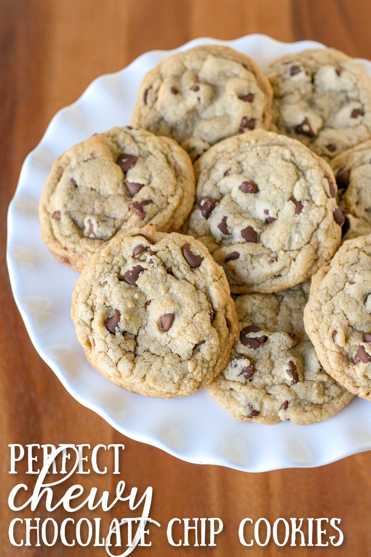 chocolate chip cookies piled on white cake stand with wood surface underneath and text overlay at the bottom