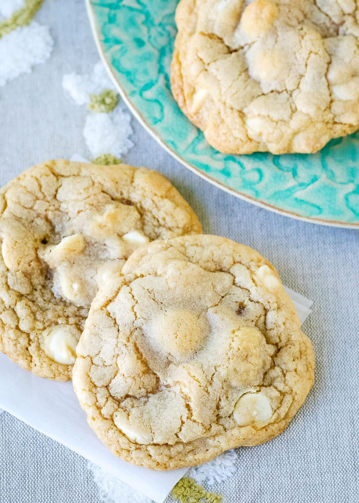 two cookies on piece of parchment and another cookie on a plate behind