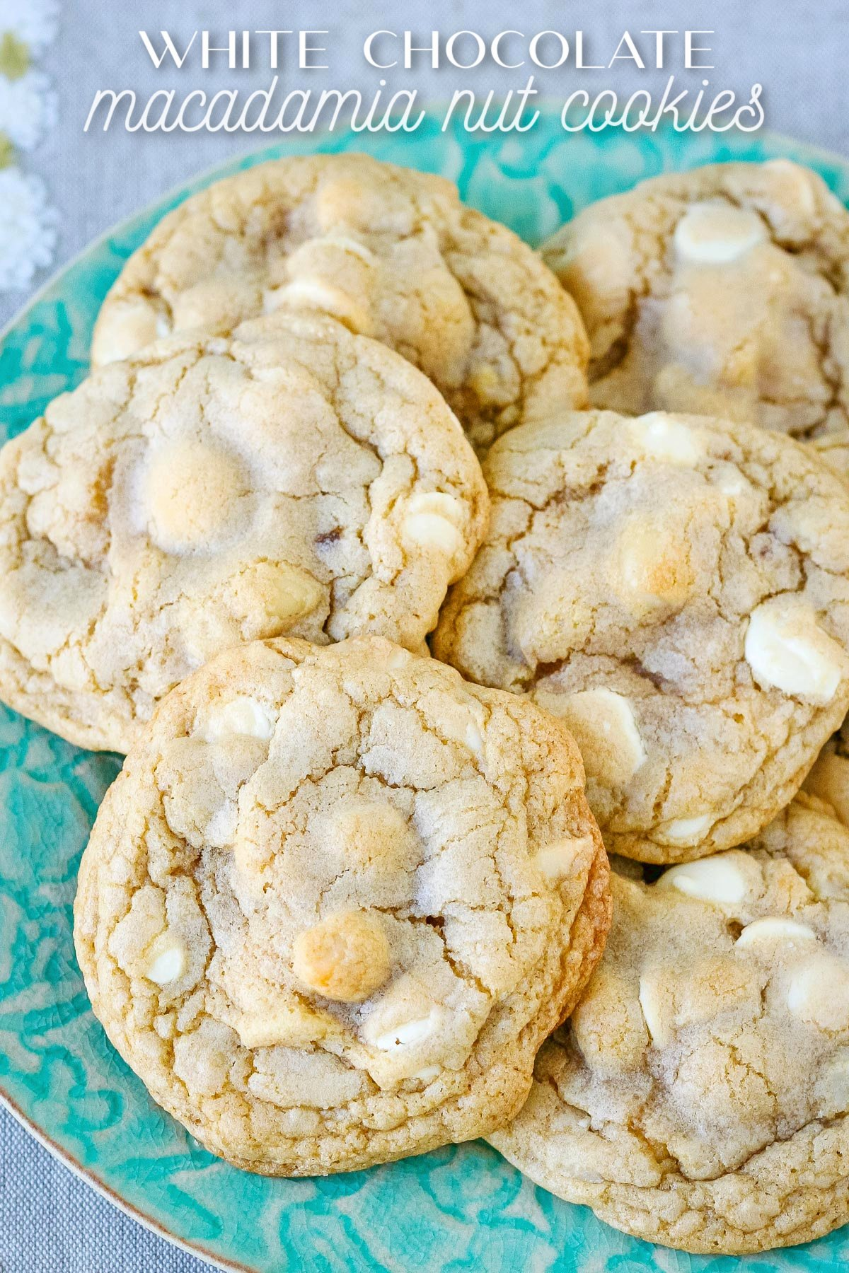 green plate piled with white chocolate macadamia nut cookies and title overlay at top of image