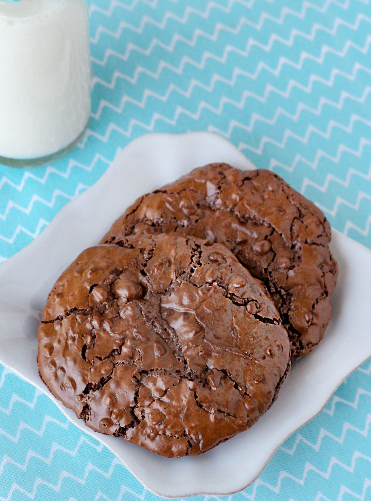 2 chocolate cookies on small white square plate