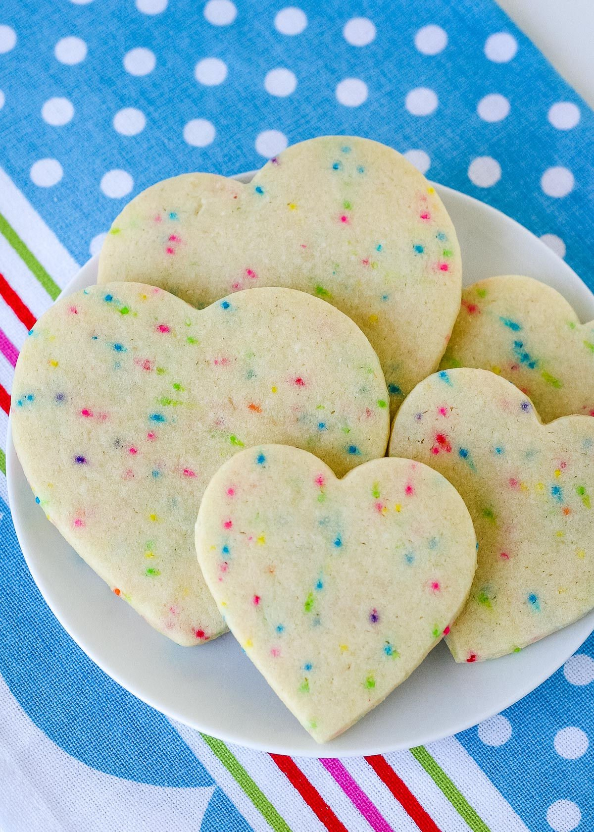 heart sugar cookies on white plate sitting on colorful blue napkin top down view