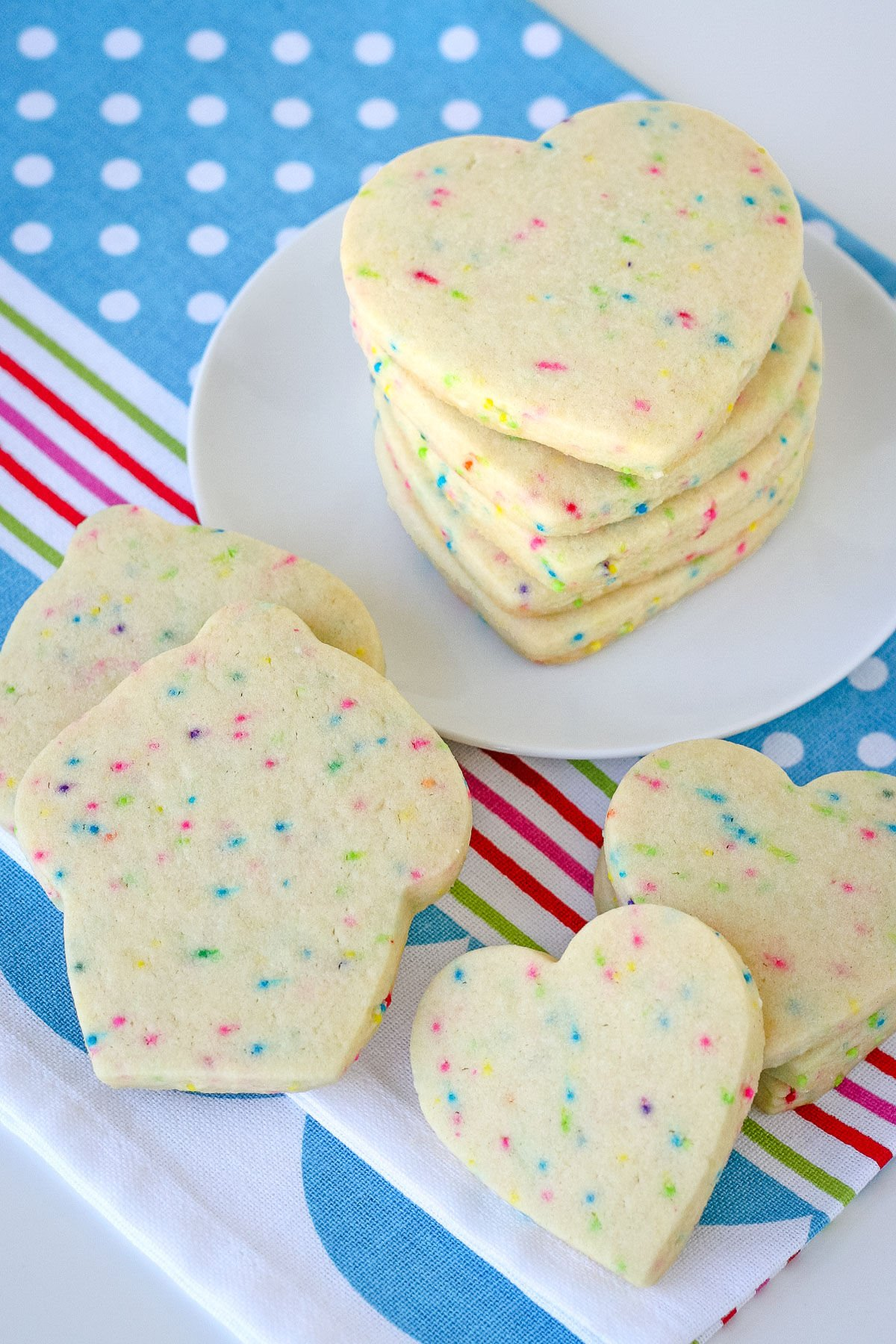 cut out sugar cookies stacked on white plate with colorful blue napkin underneath