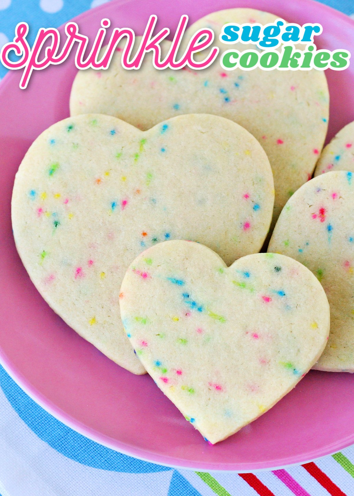 sugar cookies with sprinkles cut into heart shapes on pink plate with title overlay at top of image