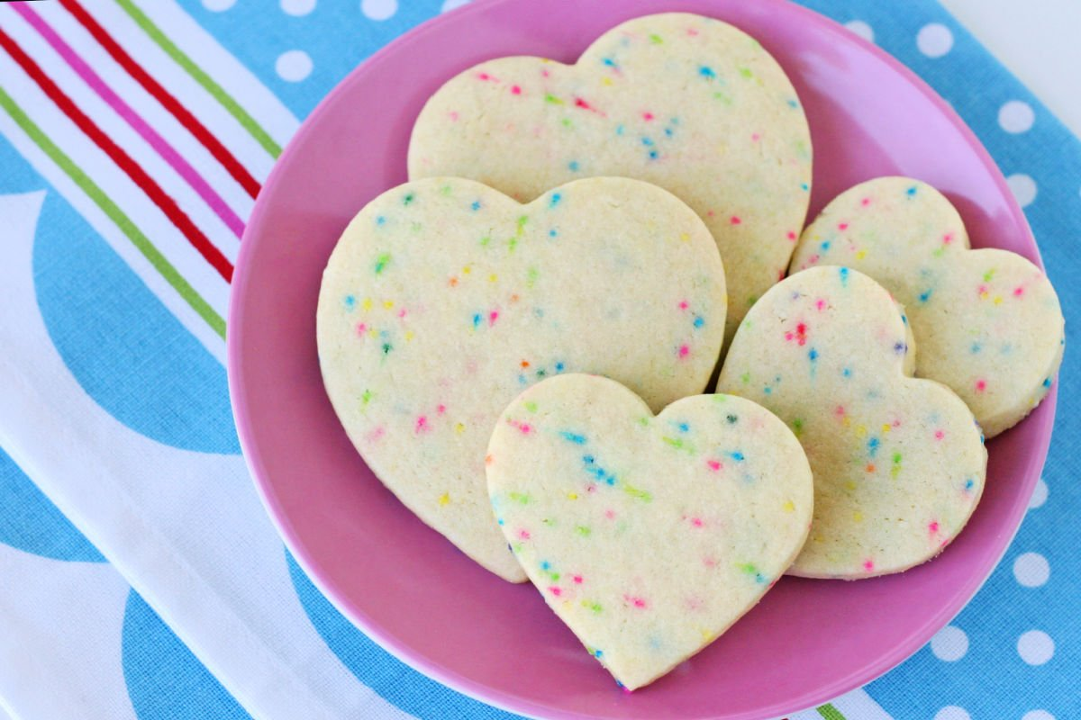sugar cookies with sprinkles cut into heart shapes on pink plate with blue napkin beneath