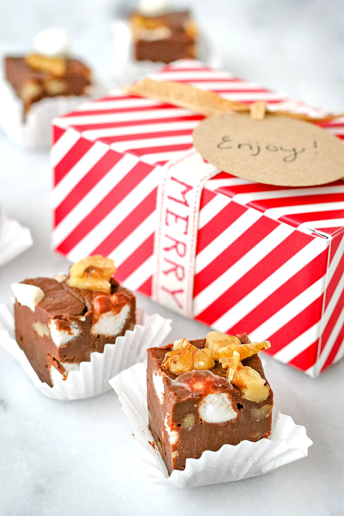 rocky road fudge pieces in white liners with red and white striped box in background