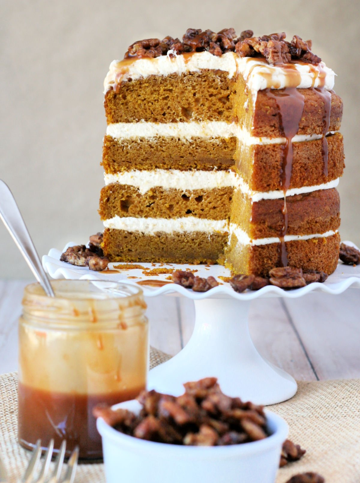 interior of pumpkin cake shown on white cake stand with slice removed