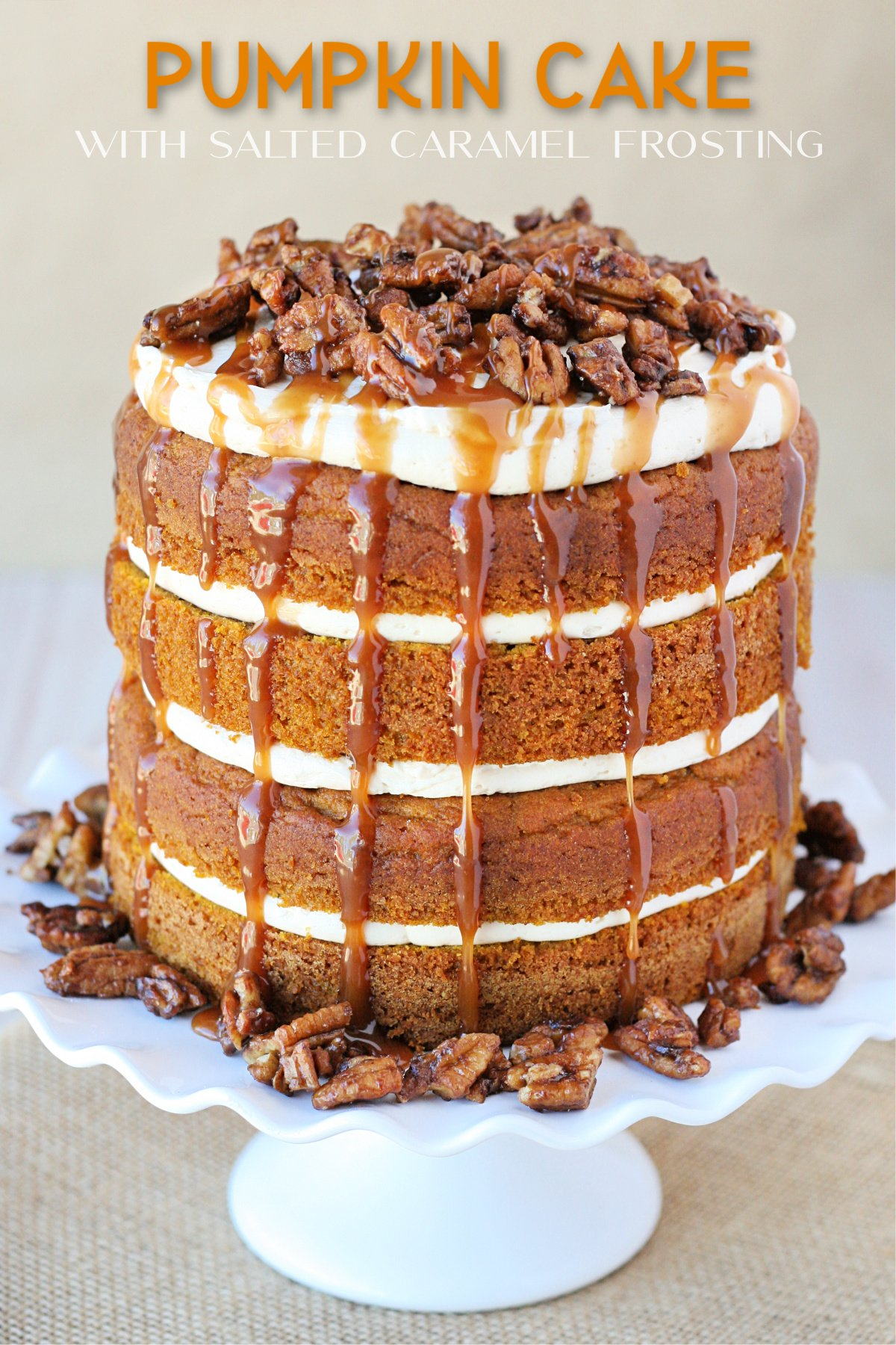 pumpkin layer cake on white cake stand with salted caramel frosting and sauce dripping from the top and covered with candied pecans text overlay at top