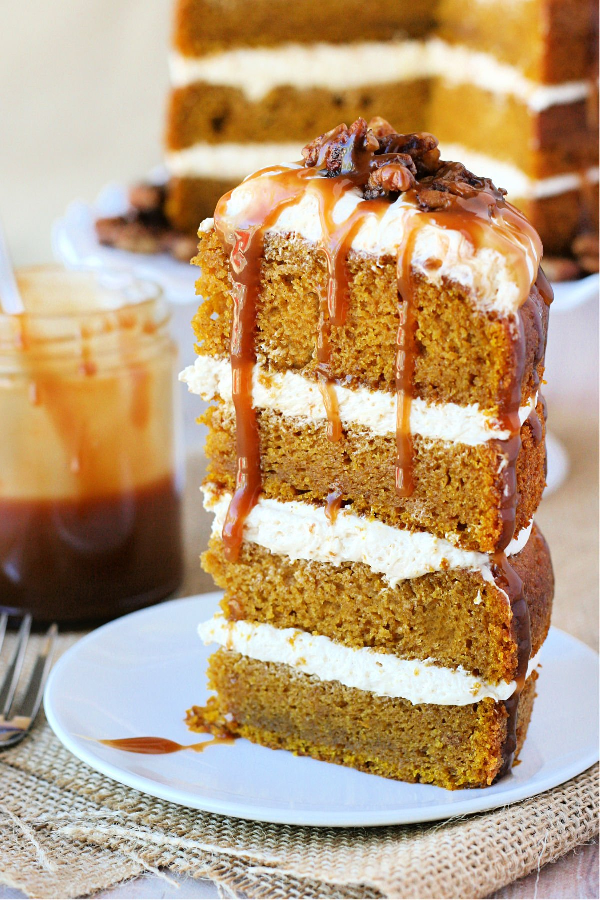 slice of pumpkin cake sitting on white plate with caramel drizzling down the sides the whole cake is in the background