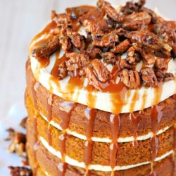 top down view of pumpkin cake with salted caramel frosting on white cake stand with candied pecans on top