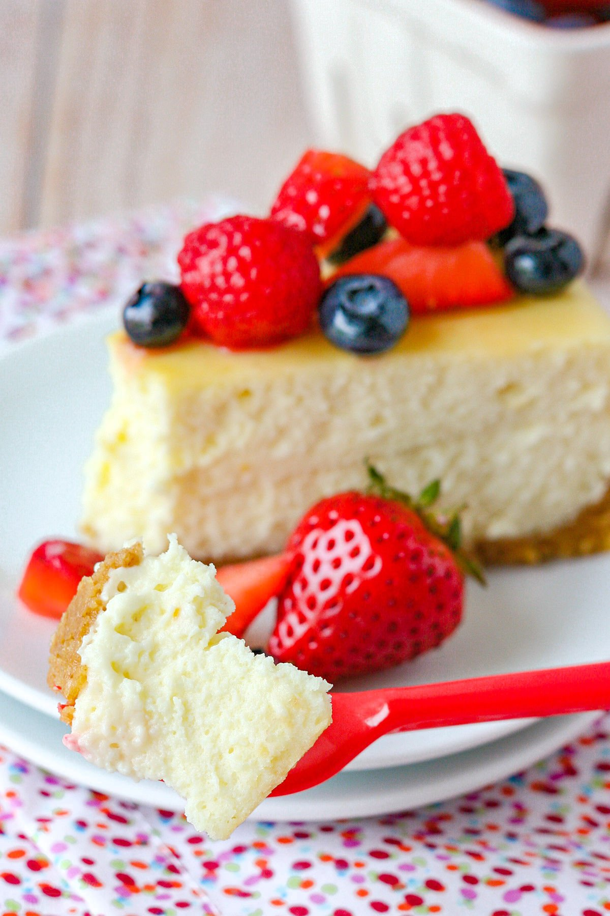 cheesecake slice on plate with one bite on fork.