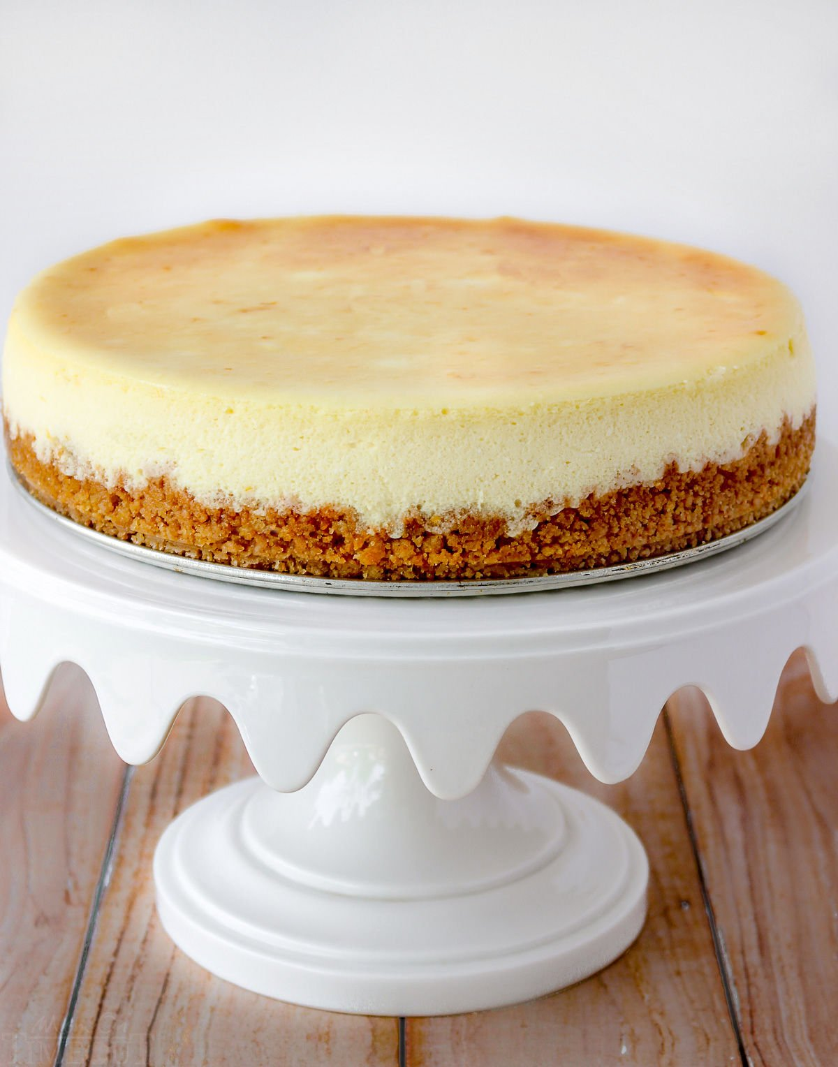 plain cheesecake recipe on white cake stand without toppings.