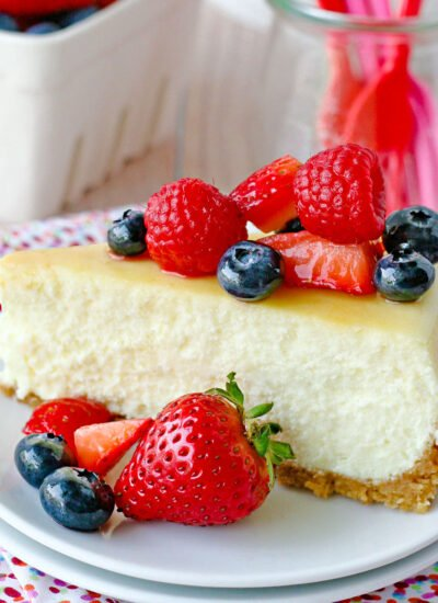 slice of cheesecake on white plate topped with fresh berries.