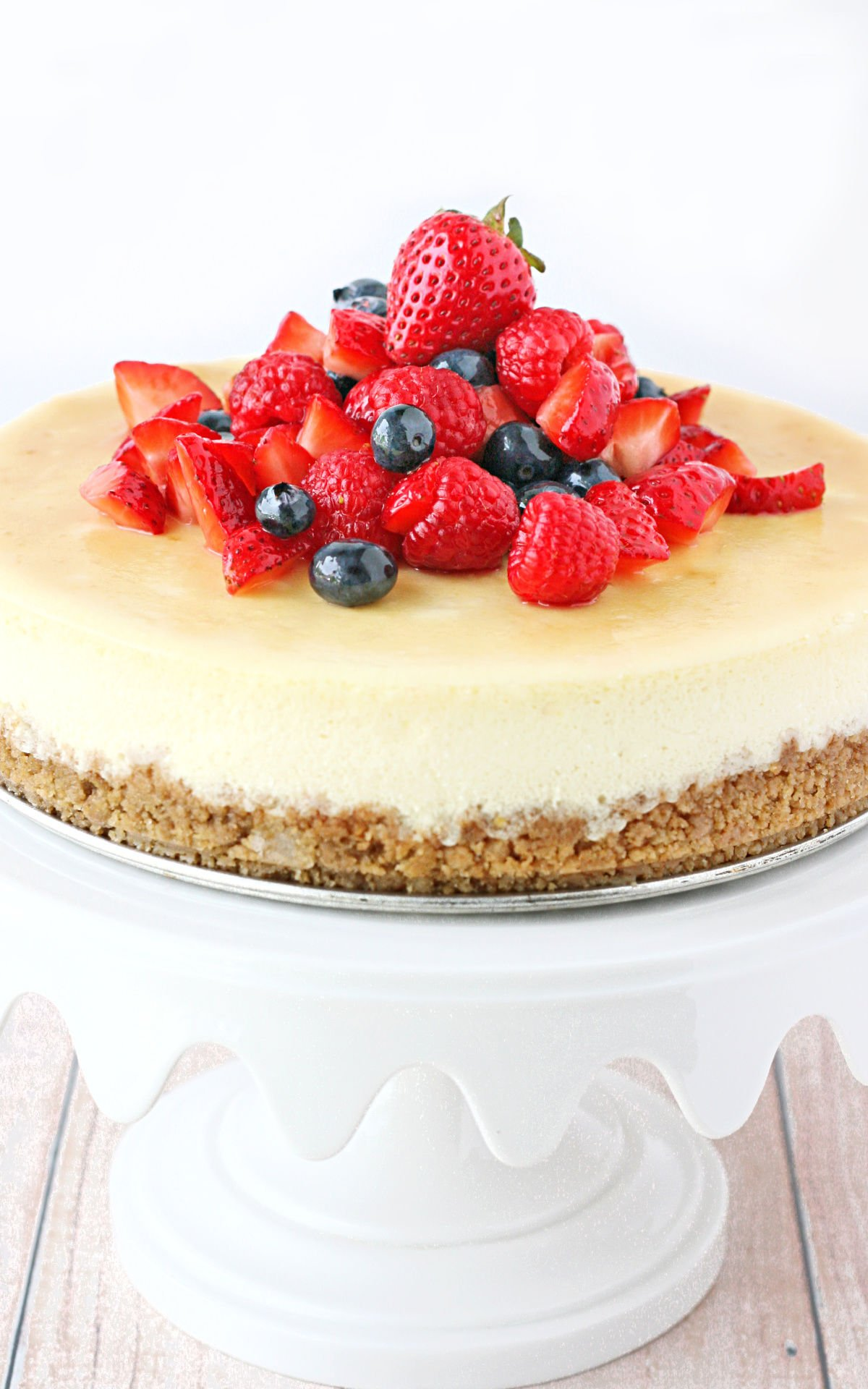 whole cheesecake on white cake stand topped with fresh berries.