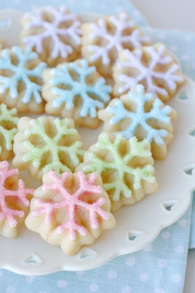 spritz cookies on white plate frosted in four pastel colors
