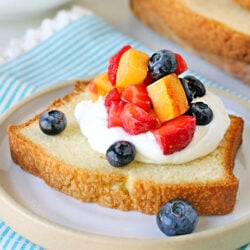 close up look at pound cake slice topped with cream and berries.